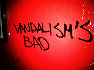 "Humorous vandalism on the wall of a bar in San Francisco, reading ""VANDALISM'S BAD""."